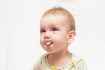 Sweet little girl with tears on her cheeks and red eyes stuck her tongue out on a white isolated background