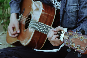 The young man plays the guitar. Visible hands and guitar