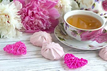 Peonies flowers pink cup of tea rattan hearts marshmallow on a white wooden background - stock image.