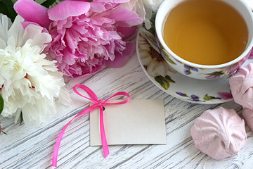 Peonies flowers pink cup of tea greeting card marshmallow on a white wooden background - stock image.