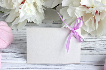 White peonies flowers with empty greeting card on a white wooden background - stock image.