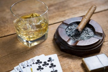 Close-up of cards by whisky and cigar