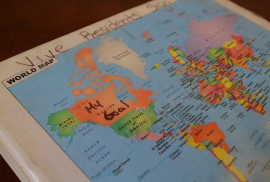 """A map of the world, with """"My Goal"""" written in ink over Canada, is seen on the residents' sign-in binder at Vive La Casa shelter in Buffalo"""