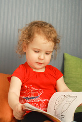 Pretty little girl leafing a picture book