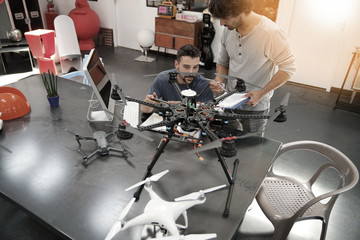 Engineer and technician working together on drone in office Wall mural