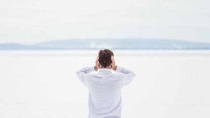Le silence est trop fort - Homme qui se cache les oreilles dans un paysage enneigé