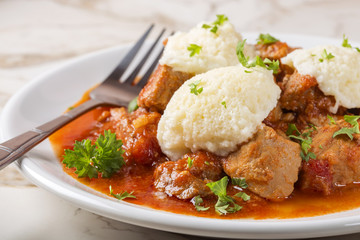 Goulash with dumplings on plate with fork