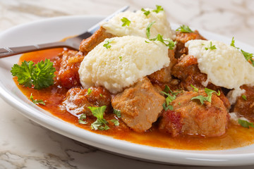 Classic goulash with dumplings on plate