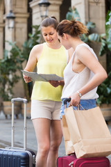 women friends having  map and searching tourist route in the city