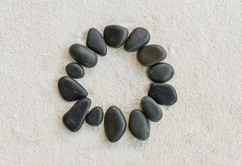 black stones forming a circle on white sand background