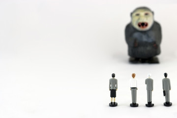 Rear view of plastic toy employees listening to the plastic gorilla boss. Shallow focus. Copy space.