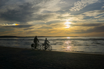people ride bikes by the sea in the sunset