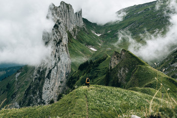Young woman in yellow rain jacket standing in front of a mountain range in Switzerland