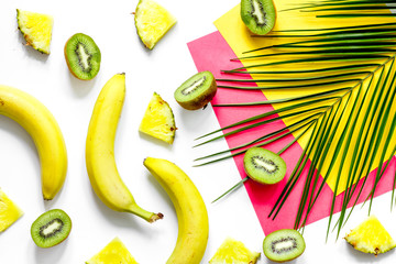 Concept of summer tropical fruits. Banana, kiwi, pineapple and palm branch on white table background top view