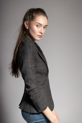 Portrait of gorgeous young caucasian attractive sexy business woman or secretary wearing checked jacket and jeans