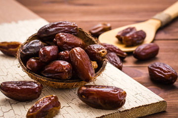 Sweet dried dates fruit in a wooden bowl and in the spoon on the table