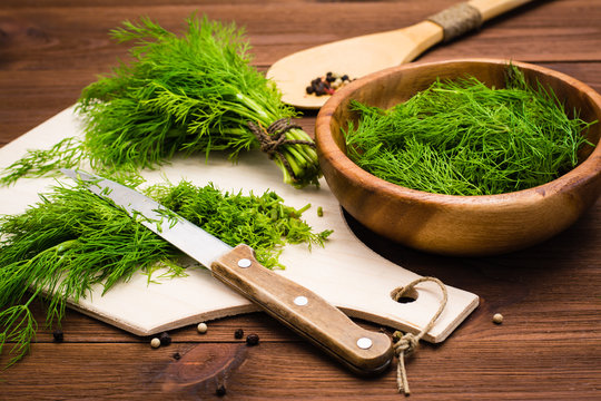 Chopped fresh dill on a cutting board and dill in a wooden bowl on the table