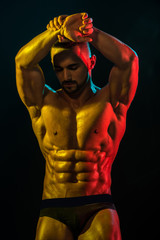 Healthy muscular young man after workout on dark background. Naked athlete with strong body.Bodybuilder and strip theme, beautiful with pumped muscles naked man posing in the studio