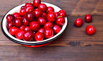Ripe red cherry in an iron bowl