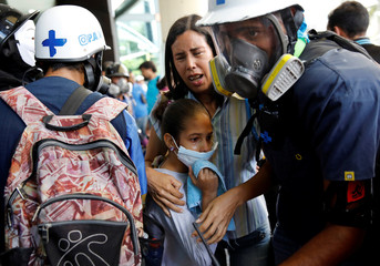 A woman and a girl get medical attention outside a shopping mall after smoke from tear gas fired by security forces got inside of it during clashes at a rally against Venezuelan President Nicolas Maduro's government in Caracas
