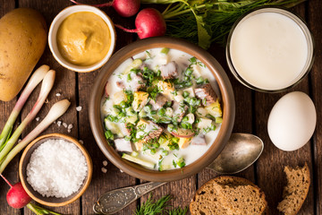 Okroshka. Traditional Russian summer cold yogurt soup in bowl on wooden background.