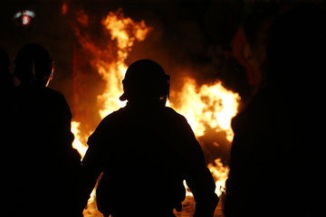 A German riot police officer is silhouetted at the front of the bonfire on the street during the demonstration during the G20 summit in Hamburg