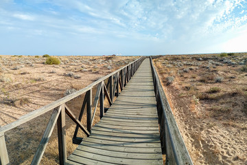 Wooden walkway over the sand dunes to the beach. Beach pathway in Huelva Beach, inside a natural area in Andalusia, Spain