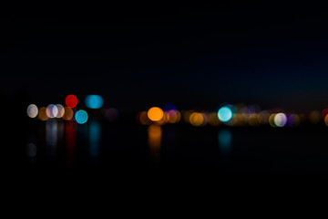 Bokeh of city night lights on water with reflection of cityscape or skyline of Baltimore, Maryland