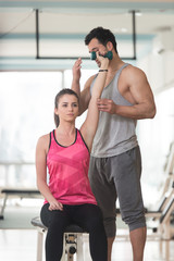 Gym Coach Helping Woman On Triceps Exercise