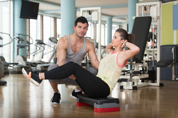 Woman With Personal Trainer On Bosu Abs Exercise