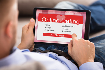 Man Using Online Dating Application On Digital Tablet