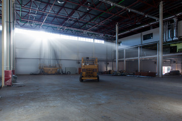 Scissor lift in a warehouse with rays of the sun