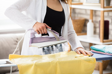 Woman Ironing Clothes With Steam From Iron