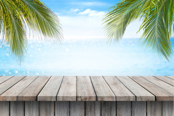 Empty wooden table and palm leaves on beach blurred background.