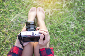 Hipster Asian tourist woman photography shoot a photo by digital camera to fields and sitting on green grass for relaxing