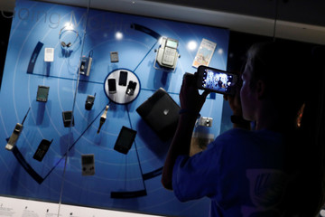 A museum-goer uses their mobile phone to take pictures of a display of older cell phones at the Smithsonian's National Museum of American History in Washington