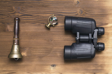 Binoculars, world globe and train conductor bell on wooden table background. Adventure or travel concept.