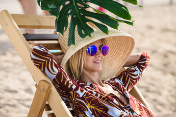 Portrait of blonde woman resting on the beach. Hat and sunglass