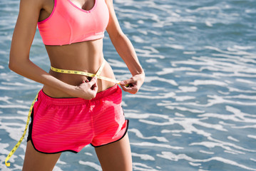 Slim sporty woman in pink shirt doing measures of her waist outdoor on the beach