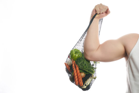 Joyful man athlete holding a shopping bag full of vegetables and flexing his bicep isolated on white background with copy space. Healthy eating and detox concept.