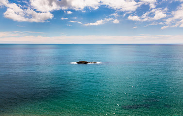 Single rocky island on calm azure blue sea.