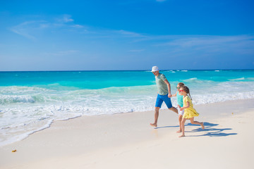 Family on white tropical beach have a lot of fun. Dad and kids enjoy holidays on the seashore. Beach vacation activity