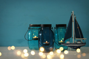 Magical mason jars whith candle light and wooden boat on the shelf
