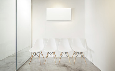 Empty office room, Glass window to the left .Loft interior style , white canvas print on the center white wall. Four white chairs at the concrete floor .