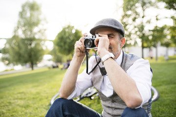 Mature businessman taking a picture with camera in park