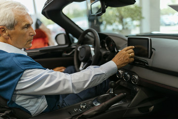 Senior man testing convertible in car dealership