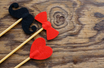 Top or flat lay view of Photo booth props a mustache, a red heart shape and a red bow tie  on a wooden background flat lay. Birthday parties and weddings.