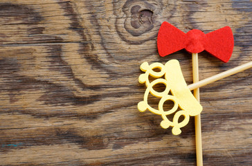Top or flat lay view of Photo booth props a red bow tie and a yellow crown on a wooden background flat lay. Birthday parties and weddings.