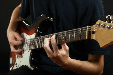 guy plays the electric guitar