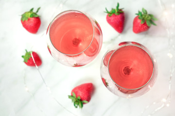 Overhead photo of two glasses of rose wine with strawberries